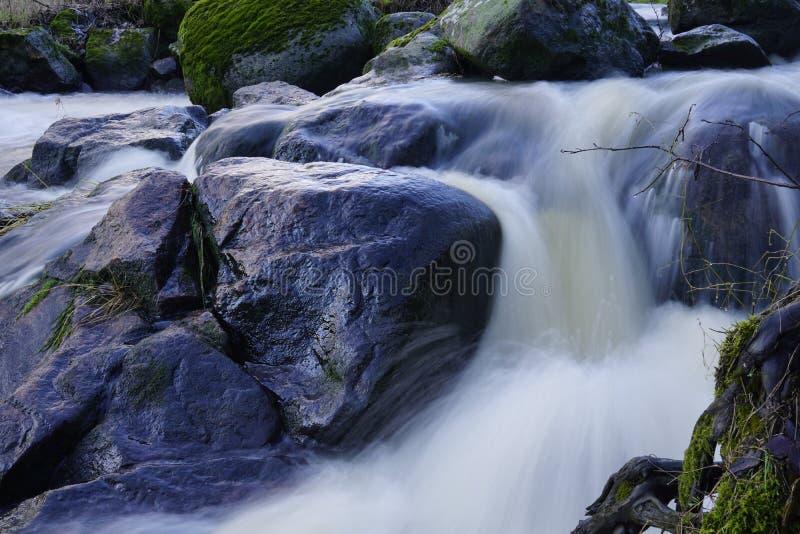 发光的湿岩石在迅速地流动的小河 免版税库存照片