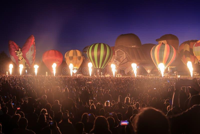 发光的热空气气球在晚上,在巨大的人群前面 免版税图库摄影