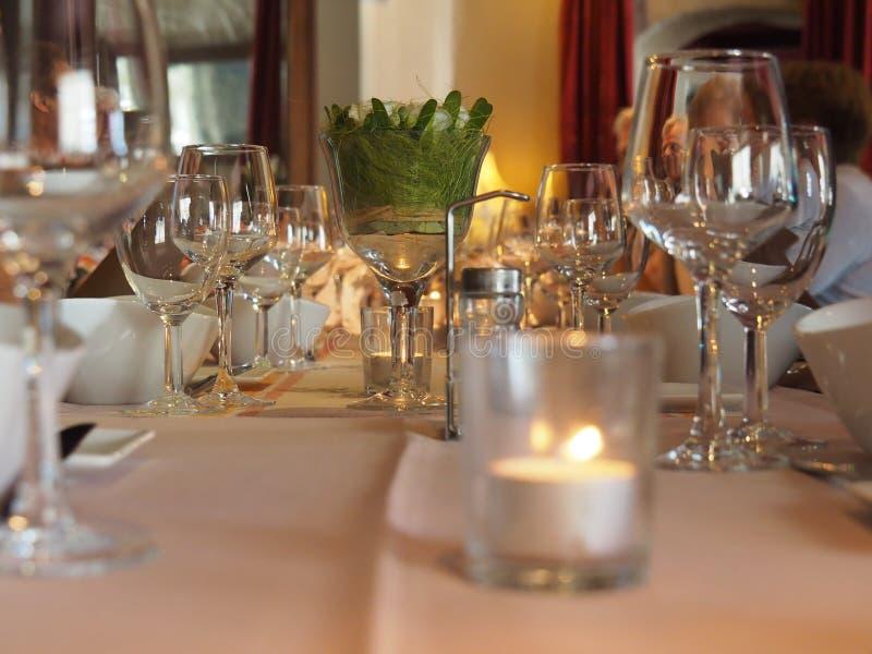 发光的玻璃和服务在一张饭桌上在餐馆 库存照片