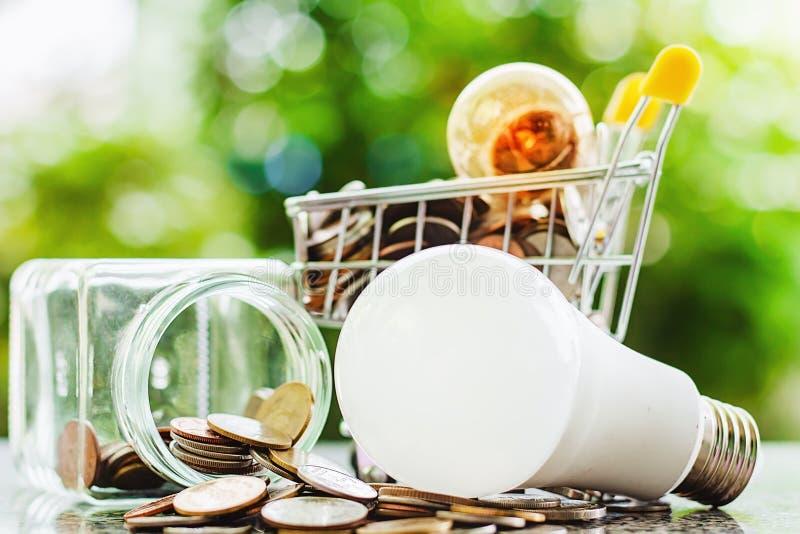 发光的电灯泡和硬币在微型购物车或台车wi 免版税库存照片