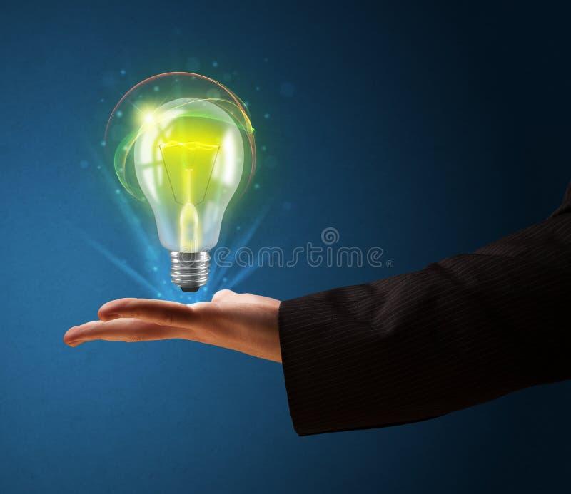 发光的电灯泡在商人的手上 库存例证