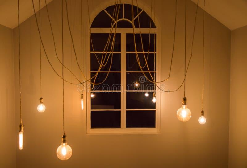 发光的电灯泡在屋子,有窗口的内部室里 免版税库存照片