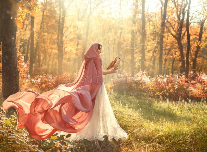 发光的白色礼服和桃子桃红色斗篷的夫人有长的火车和敞篷的 免版税库存图片