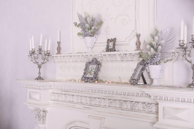 发光的白色蜡烛装饰了老白色壁炉做的照片的地方 冬天设计,斯堪的纳维亚样式 有火的客厅 库存图片