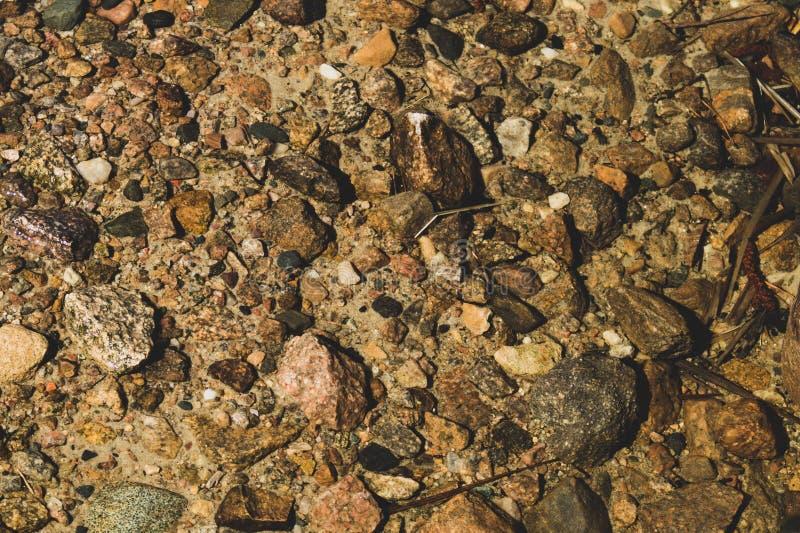 发光的透明水 与小卵石的清楚的在底部的水和石头 太阳光芒和波纹的发光的反射在 免版税图库摄影
