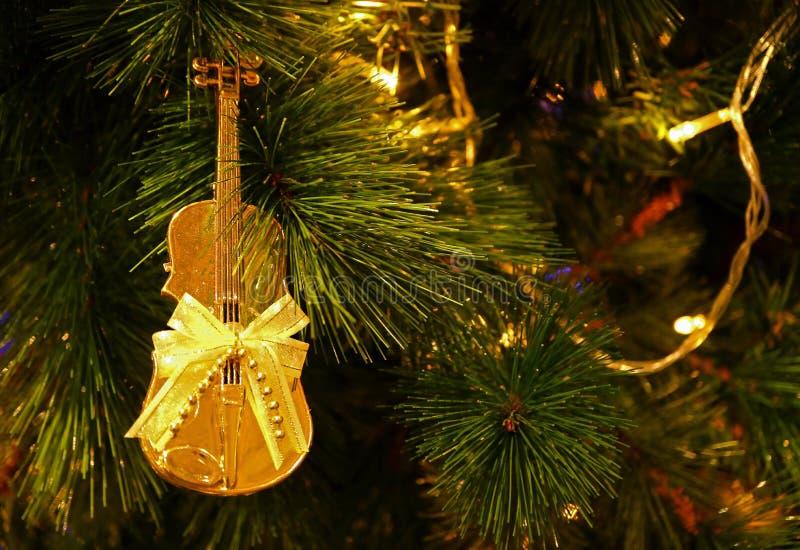 发光的金大提琴塑造与丝带弓垂悬在闪耀的圣诞树的圣诞节装饰品 免版税库存照片