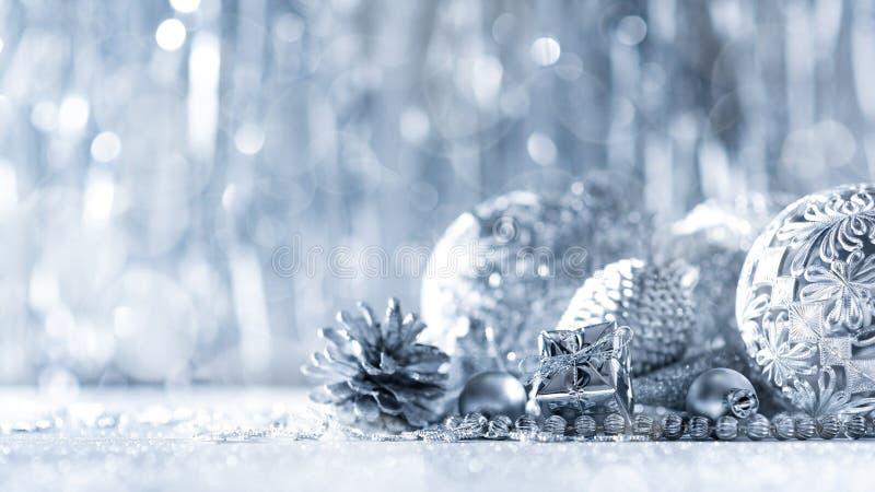 发光的银色圣诞礼物和美丽的装饰品,与defocused圣诞灯在背景中 免版税库存图片