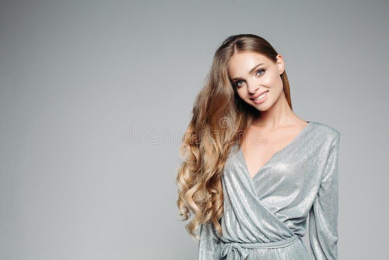 发光的银色成套装备的长发blondie妇女微笑对照相机的 免版税图库摄影