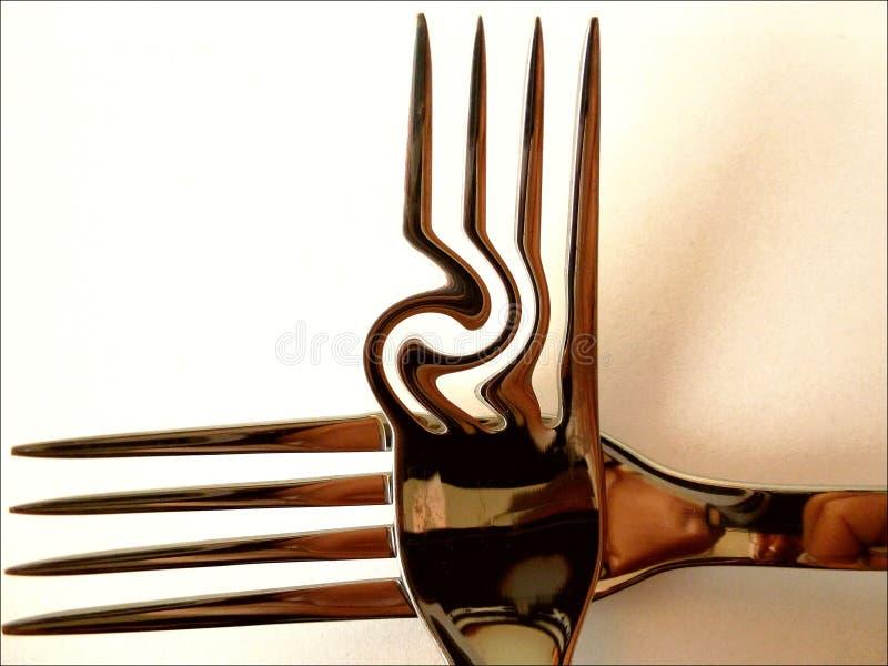 发光的镀铬物完成了在发怒形状的抽象叉子 免版税库存图片
