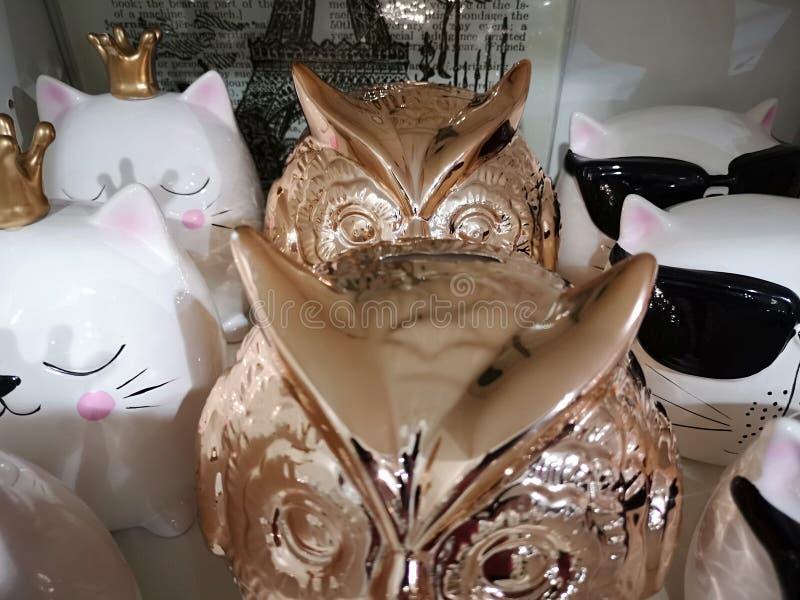 发光的陶瓷小雕象猫头鹰在架子连续逐个密封身分 库存照片