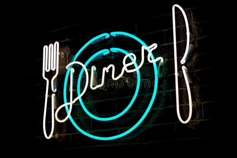 发光的霓虹题字晚餐和风格化叉子、刀子和板材 免版税库存照片