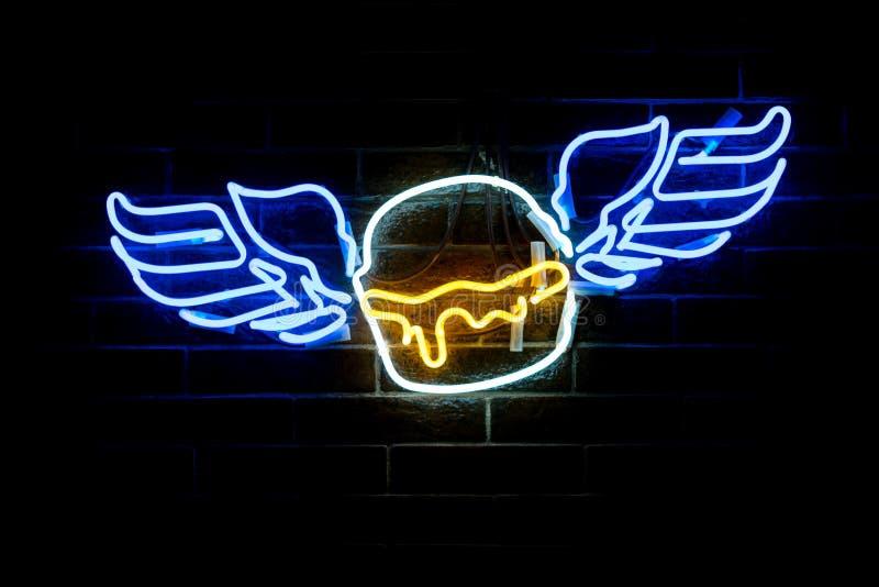 发光的霓虹风格化飞过的汉堡 免版税库存图片