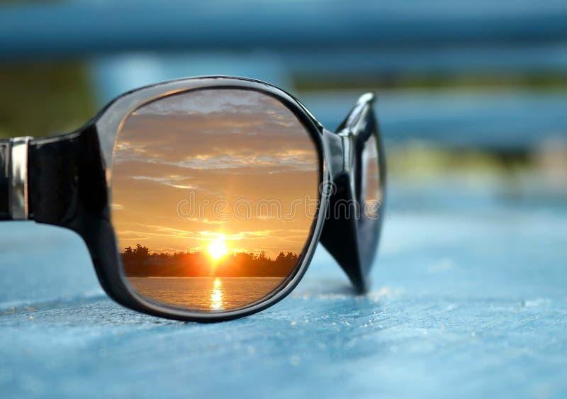 发光的黑太阳镜特写镜头有日落反射的在蓝色椅子的透镜 图库摄影