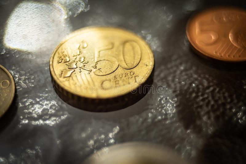 发光的50分欧元硬币关闭在玻璃桌上 免版税库存照片