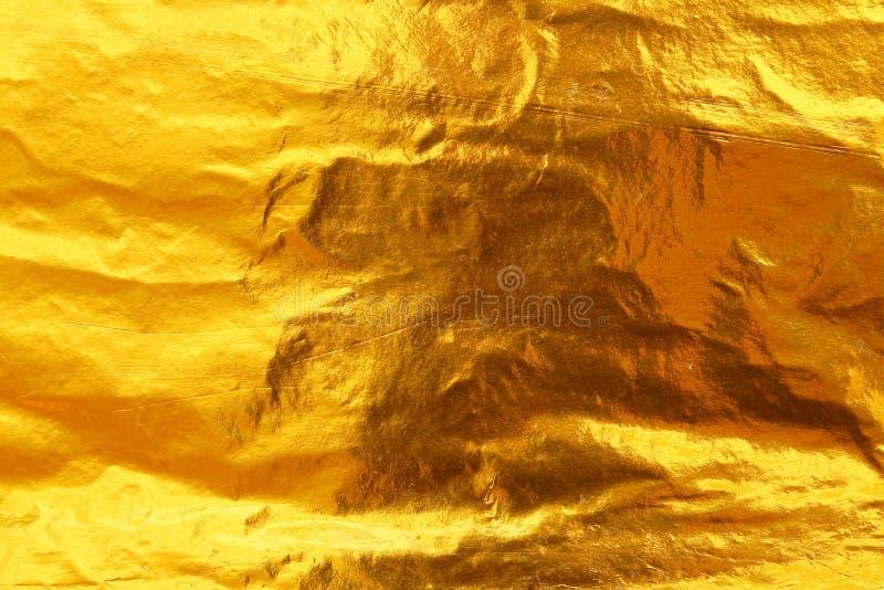 发光的黄色叶子黑暗的金箔纹理背景 免版税库存照片