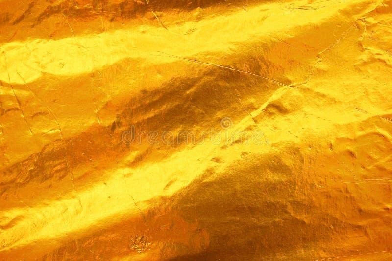 发光的黄色叶子黑暗的金箔纹理背景 免版税库存图片