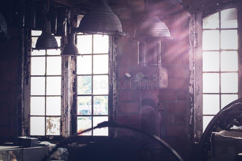 发光通过一个老被放弃的工业仓库大厦的窗口的阳光 图库摄影