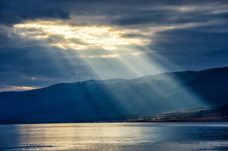 发光通过厚实的多云天空,一线希望的太阳 库存图片