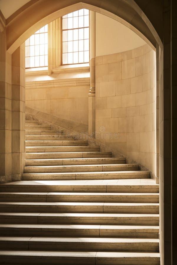 发光通过在向上弯曲通过拱道的一层经典,哥特式样式石头楼梯上的窗口的阳光 免版税图库摄影