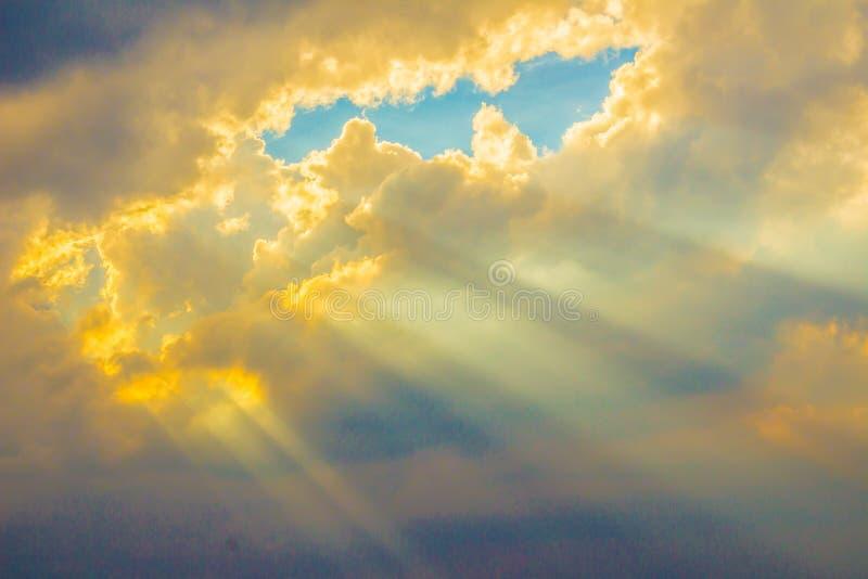 发光通过在谷的云彩的光束 与太阳的晚上日落通过云彩发出光线 免版税库存照片