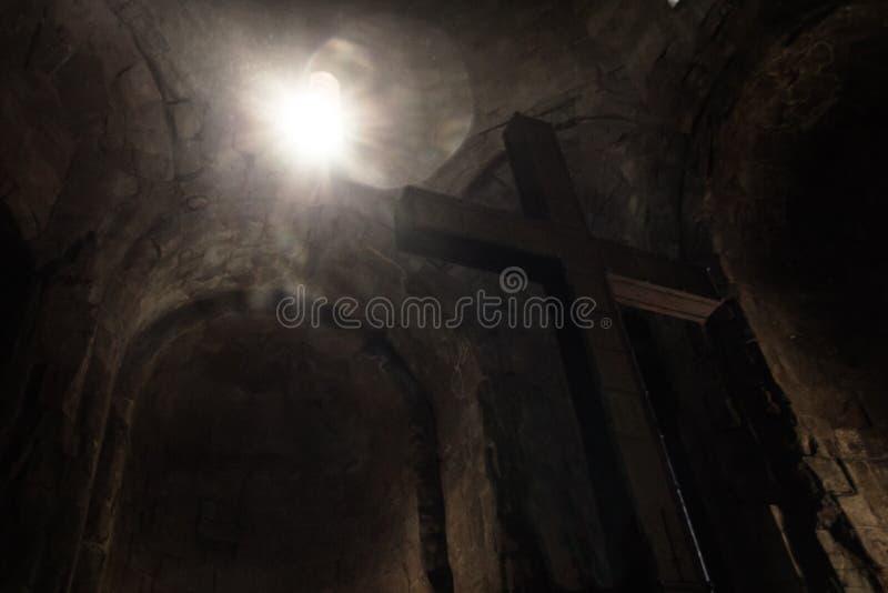 发光通过窗口的抽象太阳斑点在石十字架 免版税库存图片