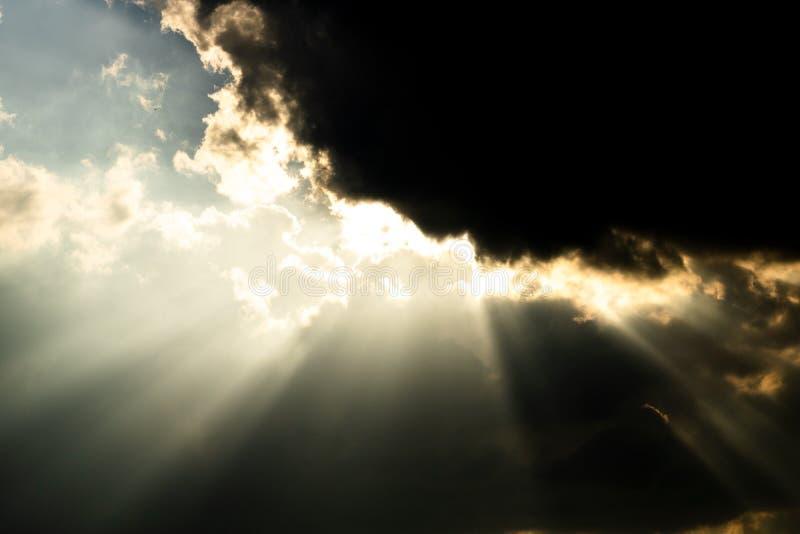 发光通过黑暗的云彩的太阳 免版税库存照片