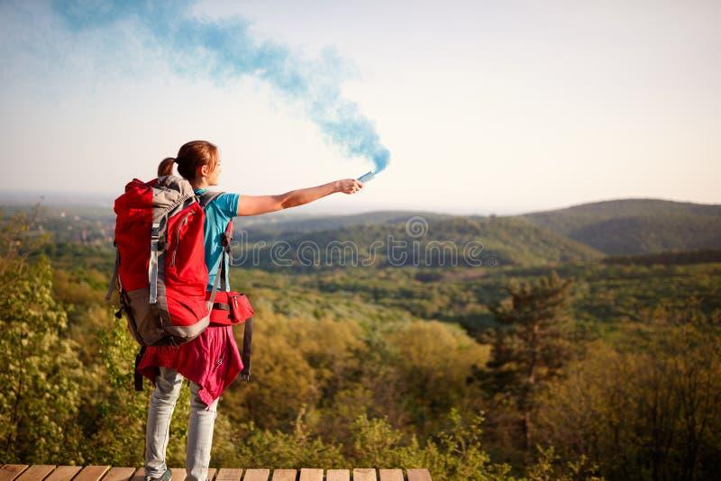发出发烟信号的女性登山家到徒步旅行者小组 图库摄影
