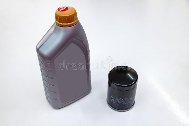 发动机过滤器的备件清洗的尘土和土的与在白色被隔绝的一个公升瓶或罐头润滑剂 库存照片