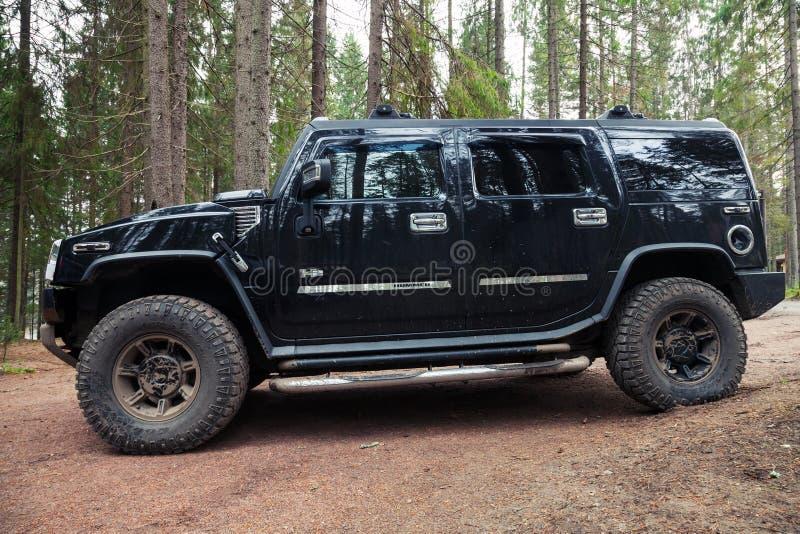 黑发嗡嗡声的东西H2车在肮脏的乡下公路站立 免版税库存照片