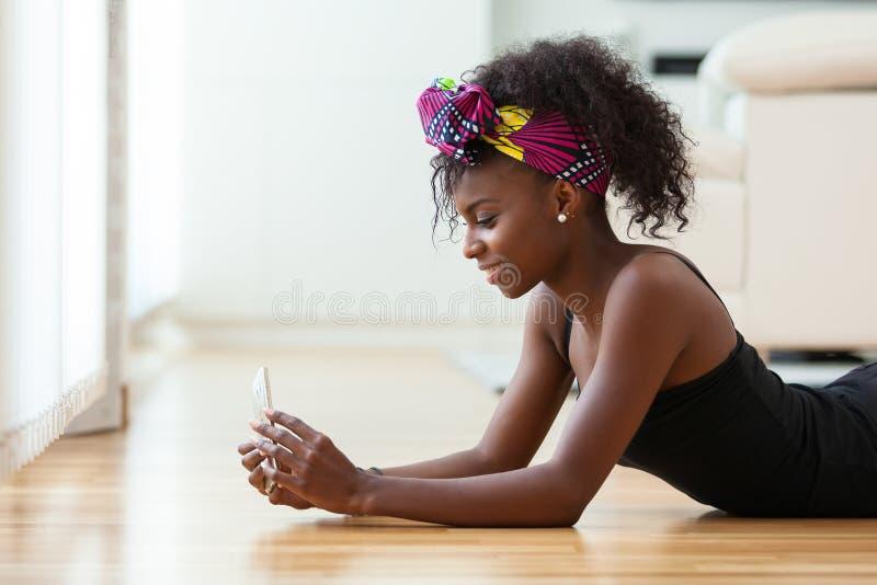 发在一个手机的非裔美国人的妇女一个正文消息 库存图片