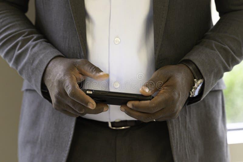 发在他的智能手机的非裔美国人的商人一个电子邮件 免版税图库摄影