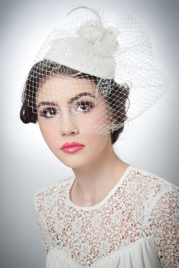 发型和组成-美丽的女孩艺术画象 有白色盖帽和面纱的图片