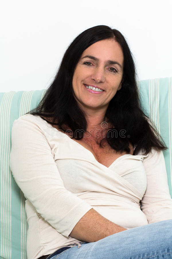 黑发妇女坐长沙发和微笑 库存图片