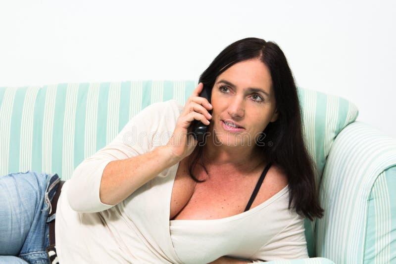 黑发妇女谈话在电话 库存照片