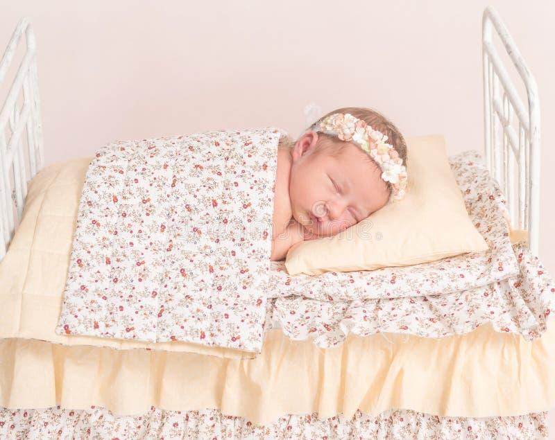 发带的婴儿小睡在板料下的 免版税库存照片