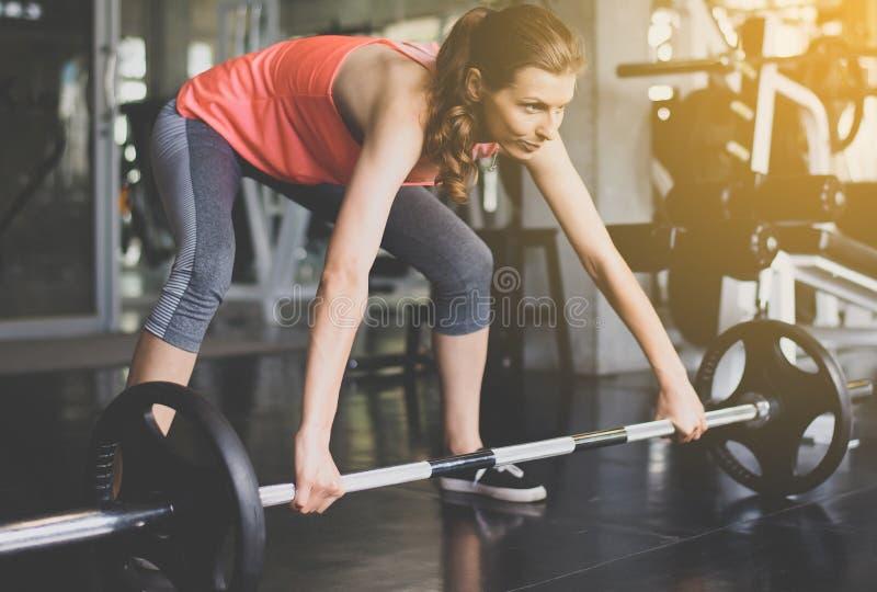 发怒适合的身体和肌肉举的杠铃重量在健身房,做锻炼训练的体育妇女 库存照片