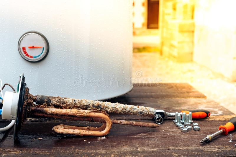 发热设备用铁锈和标度报道,与螺丝在锅炉的背景,说谎在一张木桌上 库存照片