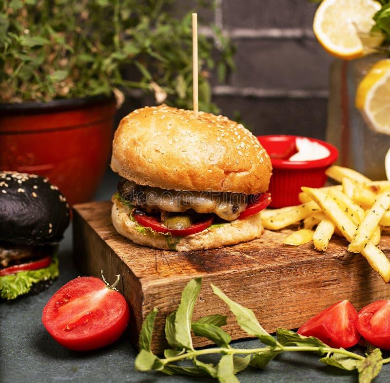 发牢骚与菜便当、薯条和番茄酱的芝士汉堡 免版税库存照片