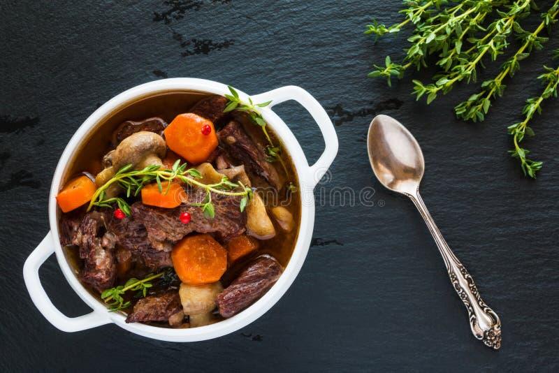 发牢骚在一个白色汤碗的村镇在黑石背景,顶视图 炖用红萝卜,葱,蘑菇,烟肉 免版税图库摄影