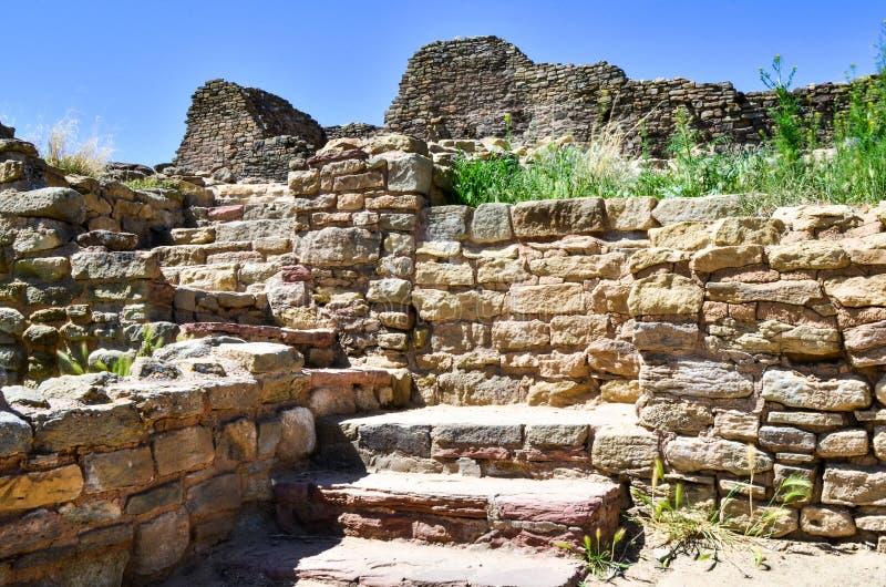 发现古老墙壁和一层楼梯对与黄色花的过去在蓝天下 免版税库存图片