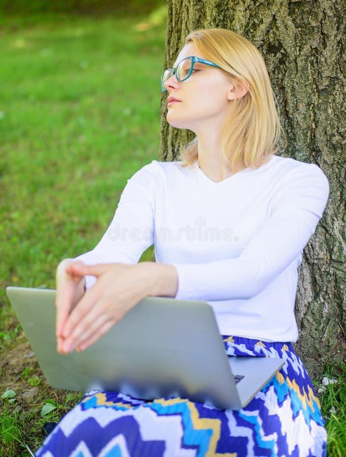 发现启发的作为分钟 学生冲浪的互联网在公园 学生准备项目 妇女膝上型计算机公园研究 免版税图库摄影
