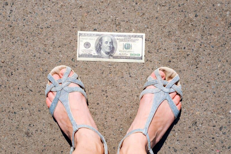 发现在街道上的幸运妇女金钱 在一百元钞票旁边的妇女脚 躺下失物招领处的金钱  库存照片