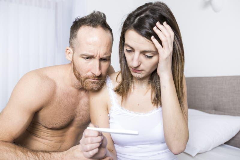 发现妊娠试验的结果快乐的夫妇坐床 免版税库存图片