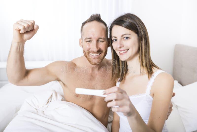发现妊娠试验的结果快乐的夫妇坐床 免版税图库摄影