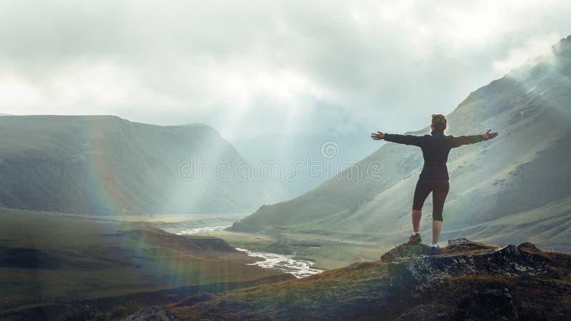 发现旅行目的地概念 有背包上升的徒步旅行者年轻女人在反对日落,后方背景的山上面  免版税库存照片