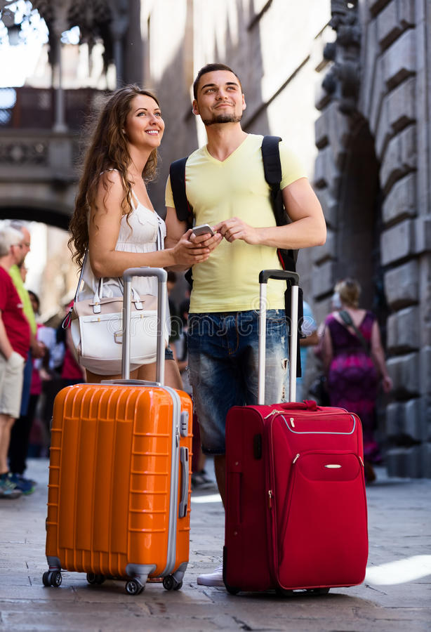 发现有电话的微笑的旅行家夫妇道路 免版税库存图片