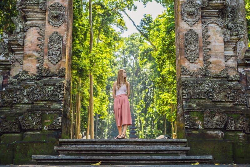 发现Ubud森林的年轻女人旅客在猴子森林,巴厘岛印度尼西亚里 旅行与儿童概念 免版税库存图片