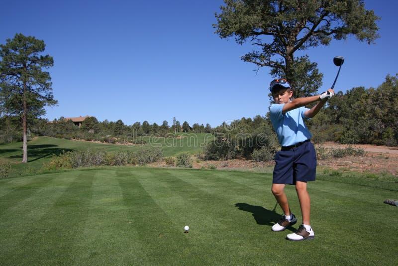 发球区域的高尔夫球运动员对年轻人 免版税库存照片