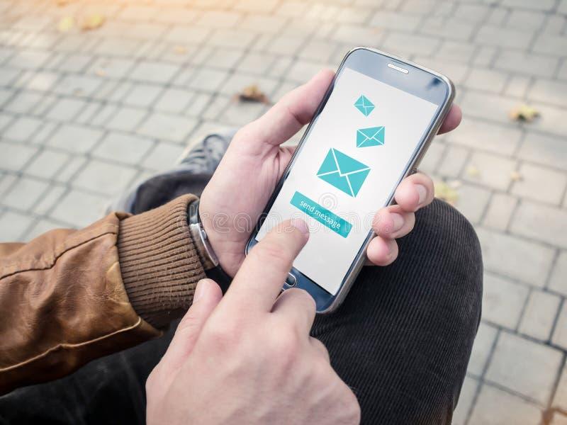 发电子邮件的商人通过现代智能手机 库存照片