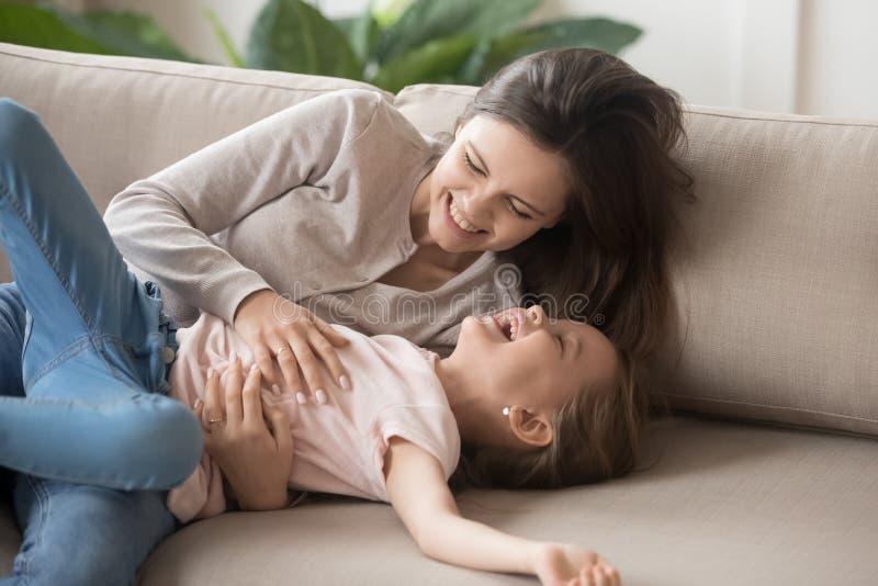 发痒女儿的笑的母亲说谎在长沙发在客厅 库存图片